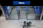 A shopper walks past a Telkom shop at a mall in Johannesburg.