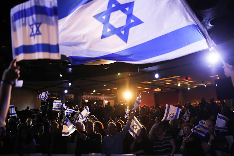 Supporters wave Israeli flags before an election campaign event with Benny Gantz, leader of Israel's Blue and White Party, in Herzliya, Israel, March 31 2019. Picture: BLOOMBERG/CORINNA KERN