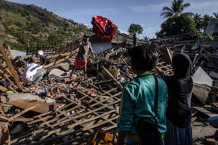 People search for their belongings at collapsed houses following earthquake in Tanjung on August 7 2018 in Lombok Island, Indonesia.