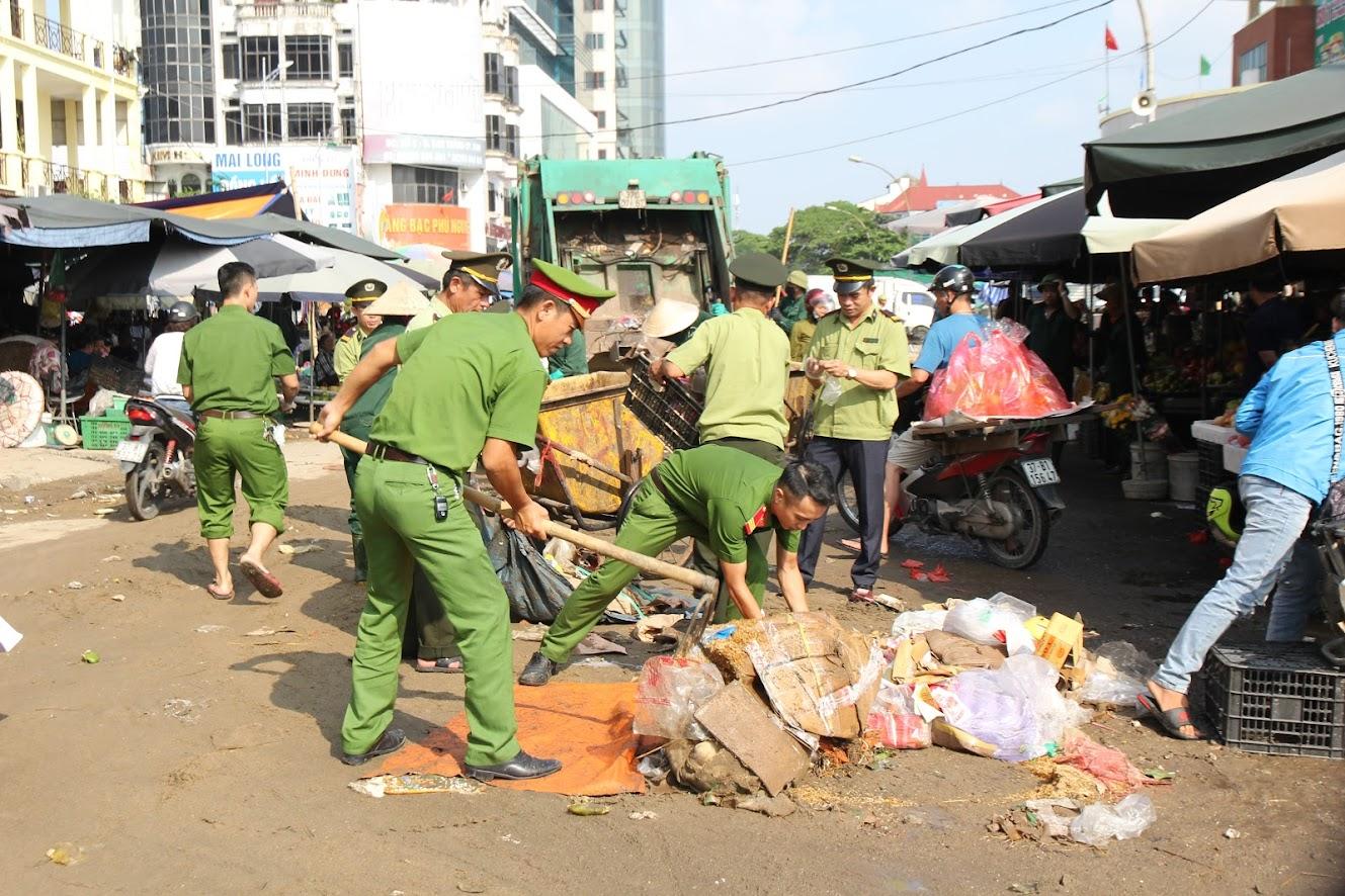 Công an phường Hồng Sơn, Tp.Vinh cùng Ban quản lý chợ Vinh dọn dẹp rác thải ngay trước cổng chợ. (ảnh: Mạnh Cường)