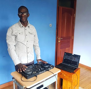 A photo of John, a tall young man, standing behind DJ turntables against a blue wall.