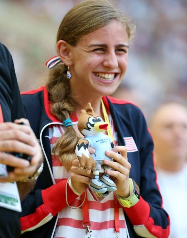 Mary Cain smiles as she holds a toy mascot at the World Championships in Moscow. (Photo John Nepolitan)