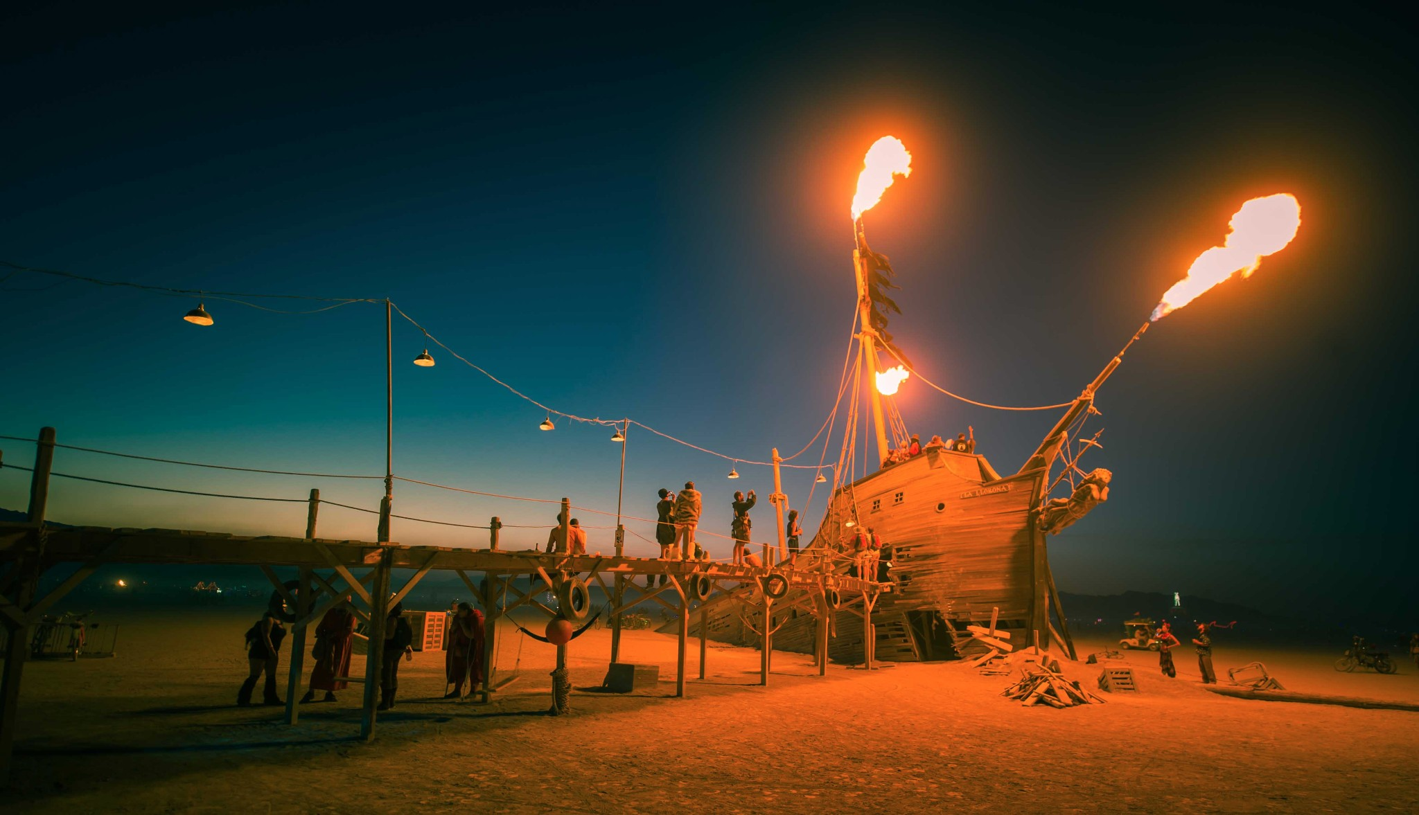Photo: The old ship blasts ragged flames just as the sun sets in the desert...