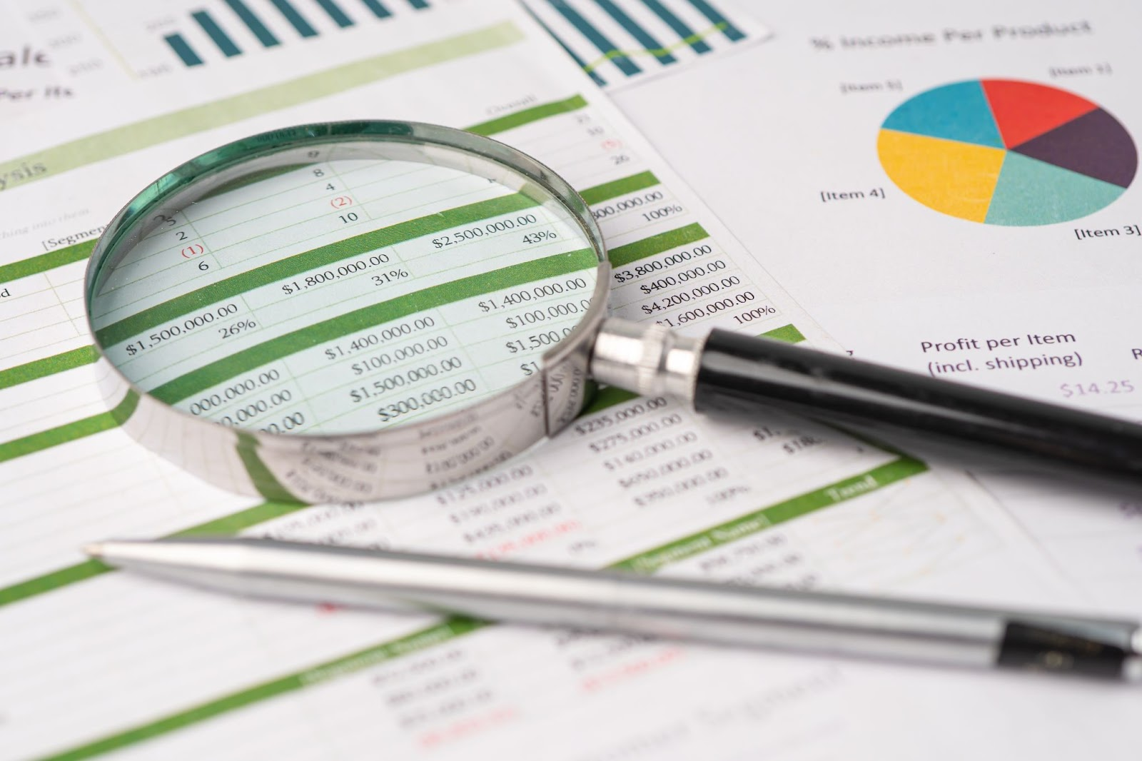 preferred stocks: Magnifying glass and a pen on top of financial statements