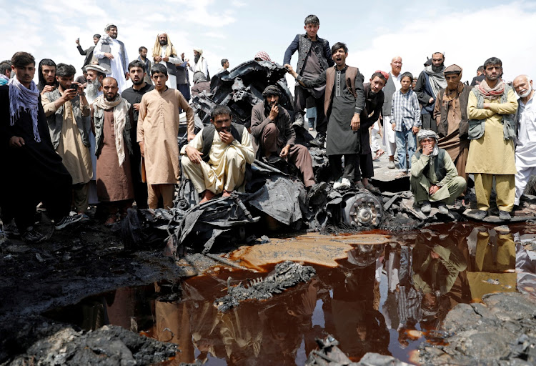 Men look at human remains following an overnight fire on the outskirts of Kabul, Afghanistan, on May 2 2021.
