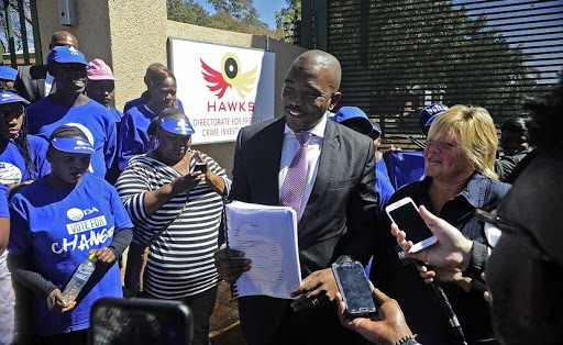 DA leader Mmusi Maimane and Glynnis Breytenbach handed over to the Hawks in Pretoria what he says is evidence of theft of public funds at the Estina Dairy Farm in Vrede, Free State. Photo Thulani Mbele.