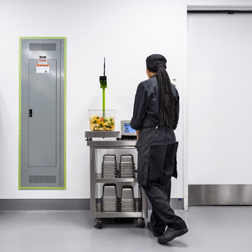 Back of a person in black scrubs weighing food on a grey metal cart