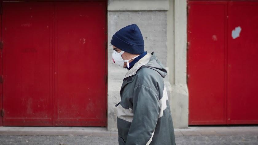Una persona anda por la calle con mascarilla.