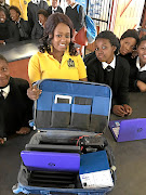 Technology entrepreneur Palesa Mahlatji displays her gadget, Solar Lab In A Bag, to pupils.