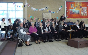 Photo: De leden van het oecumenisch koor o.l.v. Annelie Schell nemen plaats.