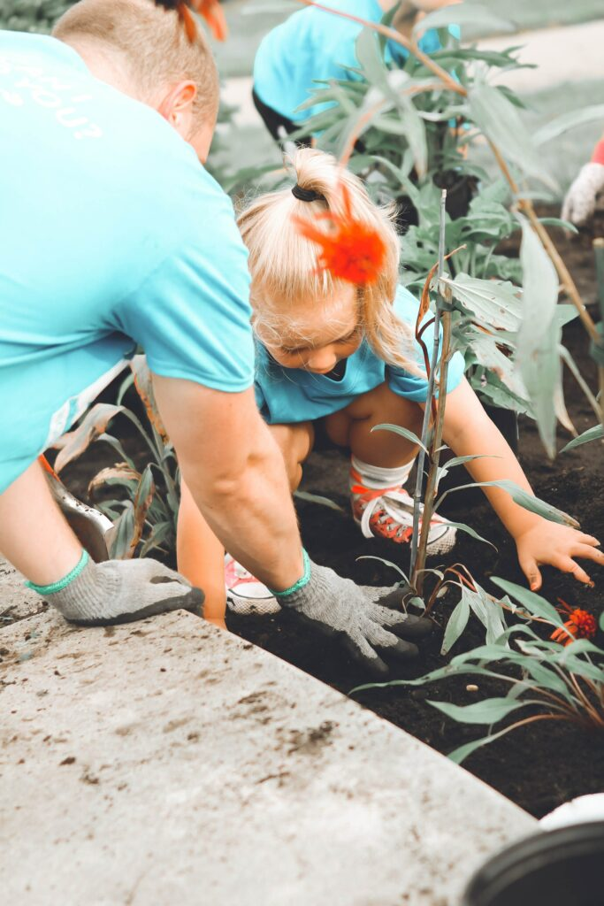 Dad and daughter are planting a flower in a garden, working cooperatively and by so doing positively impacting her body image.
