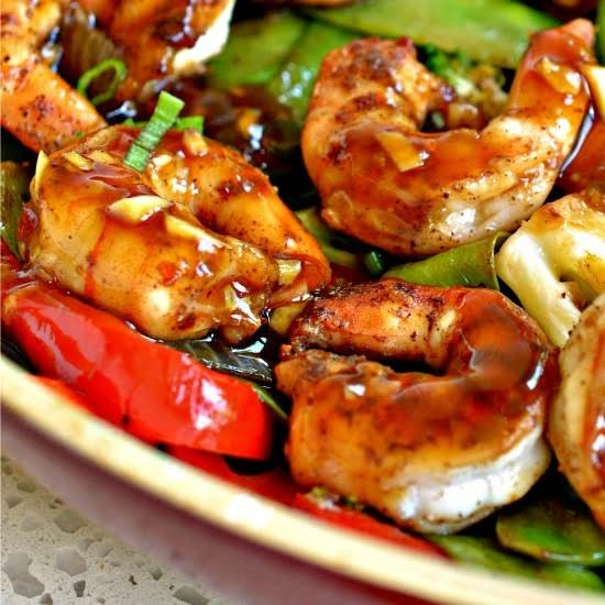 An Easy One Skillet Stir Fry Recipe With Shrimp, Red Peppers, Onions, Broccoli, Snow Peas And A Salty Sweet Garlic Ginger Asian Sauce.  Serve Over Rice Or Zucchini Noodles For A Complete Meal.