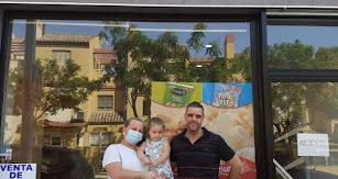 Pablo y Rocío junto a su hija en la puerta de su negocio.