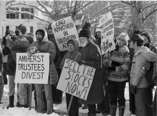 """(Alt text: Students and faculty protest the college's investments in the South African apartheid in 1977, carrying signs that read: """"Amherst Trustees Divest""""; """"End Apartheid in South Africa""""; """"Boycott Multinational Corproations in South Africa""""; """"Sell the Stocks Now!"""")"""