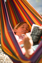 Photo: Young woman writing in journal while sitting in hammock on Jackson Lake. Grand Teton NP, WY.