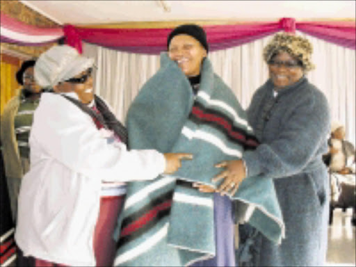 CUDDLY: Lucy Thusi, left, and Sarah Magoro, right, both of Simunye Mbokodo, wrap a blanket around 70-year-old Catherine Zulu . Pic: Penwell Dlamini. 27/06/2009. © Sowetan.