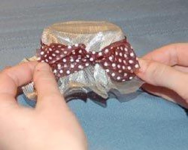 Decorate the hat by wrapping a length of ribbon around the hat, and securing...