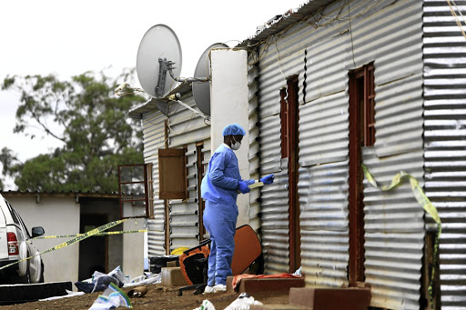 A member of the forensic team gathers evidence at the scene where seven people were gunned down during a raid at the Mancoba church premises in Engcobo last month.