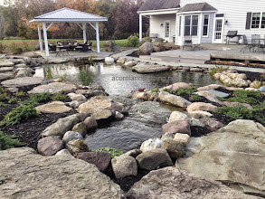 Photo: Large Backyard Waterfall #Pond | Patio Monroe County Rochester NY  Acorn Ponds & Waterfalls 585.442.6373 Certified Aquascape Contractor since 2004 can help you to create the garden of your dreams. Contact us now: www.acornponds.com  Are you looking for some landscape ideas for your backyard? Check out this beautiful large #WaterfallPond design and installation in Monroe County, Rochester NY by Acorn Ponds & Waterfalls.  This Pond is 6 feet deep, it has wetland filtration and an intake bay. This amazing Pond is big enough to swim in but without the maintenance and costs of a pool. It can be enjoyed 365 days a year and nights too after the LED Landscaping we installed. A natural stone patio with pavilion provides a sheltered living room to sit, relax and watch the fish, frogs , butterflies and dragon flies. Have dogs? No problem, they will love it.   For more info on Ecosystem Garden Ponds, click here: www.acornponds.com/ponds.html  For more info on this project click here: www.facebook.com/notes/acorn-landscaping-landscape-designlightingbackyard-water-gardens/aquascape-ecosystem-waterfall-pond-construction-pond-design-bluestone-patio-monr/607660449271081  Click HERE to get a Quote! www.acornponds.com/contact-us.html  For more info on Wetland Filtration click here: www.facebook.com/notes/acorn-landscaping-landscape-designlightingbackyard-water-gardens/wetland-filtration-waterfall-wetlands-biological-filtration-pond-filtration-bog-/248374455199684  Click here to view Testimonials from our past clients: www.facebook.com/note.php?saved&preview&note_id=473591519344642  Service areas: Monroe County, Rochester NY, Brighton NY, Pittsford NY, Webster NY, Penfield NY, Greece NY, Irondequoit NY, Victor NY, Henrietta NY, Fairport NY