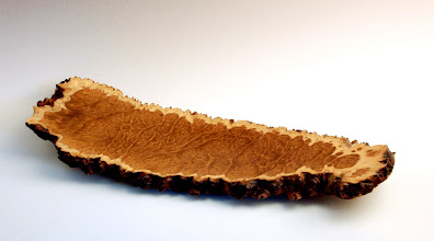 "Photo: Juror's Choice -- Jeff Bridges -- Brown Mallee Burl Platter -- 1"" X7"" X 17"" -- $225 -- Juror's Statement: This artwork gives a new beauty and presence to the standard cheese plate. The craftsmanship is excellent and the smooth and rough surface combination lends it a quiet strength."