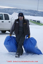 Photo: Saturday February 17th 2007 At Merrill field in Anchorage, Volunteer bush pilot Mike Petrie moves bales of straw to his plane to fly them  out to some of the first checkpoint along the Iditarod Trail in preparation for the 2007 Iditarod sled dog race.