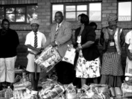 WARMTH: Nkomazi executive mayor Johan Mavuso hands over food parcels and blankets to children and families affected by HIV-Aids after a week-long municipal conference focused on, among other things, the needs of child-headed households. Pic. Alfred Moselakgomo. 16/04/08. © Sowetan.