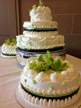 Photo: Bold & beautiful wedding cake featuring a 3-tier & two side cakes. Custom border per photo provided by bride. Fresh flowers on top w/apple green & black ribbon wrap.