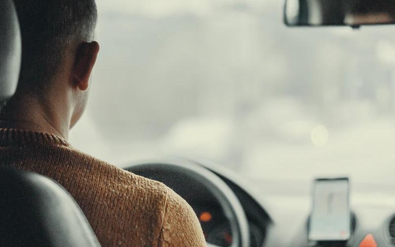 Homem de costas dirigindo