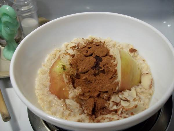 A Bowl Of Oatmeal With Apple, Almonds And Cinnamon.
