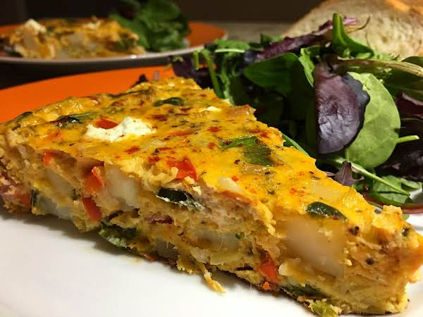 A Slice Of Frittata On A Plate With Salad Next To It.