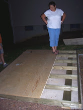Photo: A couple of days after the shed's delivery, my brother, his fiance and my mom came over to help start assembling the floor. I didn't think to take a shot of us hammering the floor's frame together, but I did snap this picture of my mom, checking out the floor, with one of the plywood pieces on it. You can see the floor is already on the concrete pad and what the frame looks like.