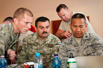 Photo: U.S. Air Force Capt. Fernando Nacionales, right, reviews a schedule of construction tasks to be completed with Croatian army members at an elementary school in Ogulin, Croatia, June 23, 2014. The school bathrooms are being renovated by Airmen from the 133rd and 148th Civil Engineering Squadron, and 219th RED HORSE Squadron in partnership with the Croatian army. Croatia is a Minnesota state partner under the National Guard State Partnership Program. (U.S. Air National Guard photo by Staff Sgt. Austen Adriaens/Released)