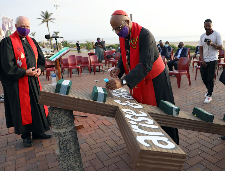 Cardinal Wilfred Napier places flowers on a cross to honour health workers, which was the theme of a beachfront Good Friday service in Durban.