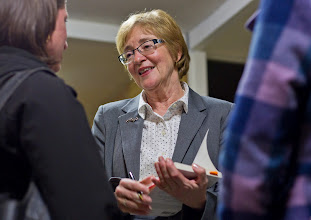 Photo: Maude Barlow prepares to autograph a book at a reception following the opening of the symposium.