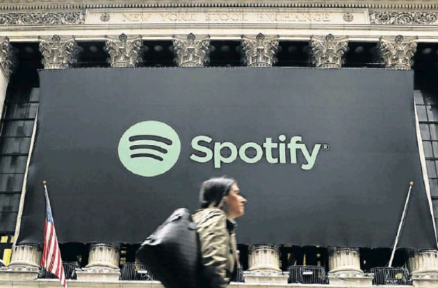 Pedestrians walk past a banner with the Spotify logo as the company lists its stock on the New York Stock Exchange with a direct listing in New York Picture: Reuters