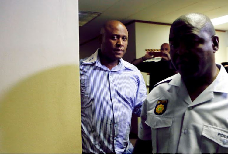 Captain Morris 'KGB' Tshabalala, who allegedly defrauded a secret state slush fund, is escorted by a police officer moments after appearing at the Commercial Crimes Court in Pretoria on 18 January 2018.