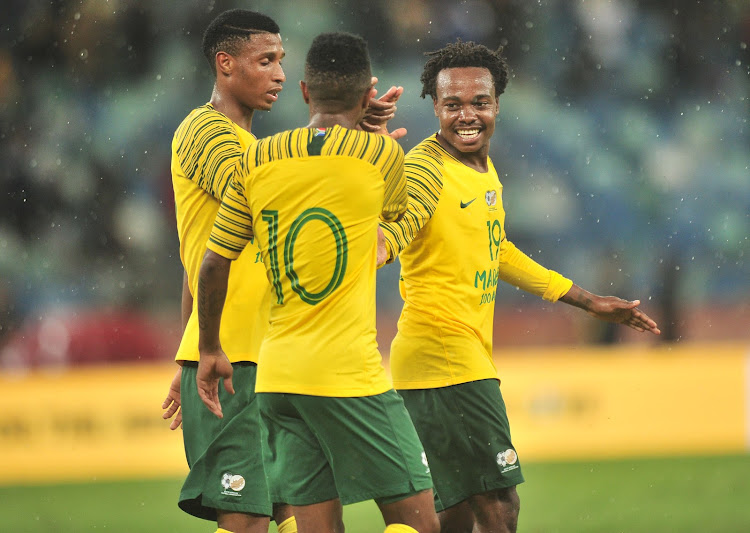Bafana Bafana striker Percy Tau (R) celebrates with teammates Thulani Serero (C) and Vincent Pule (L) during the Nelson Mandela Challenge match between South Africa and Nigeria at FNB Stadium on November 20 2018.