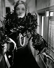 Photo: This is more a production still than a star portrait: Marlene Dietrich wears her costume from SHANGHAI EXPRESS and stands in what seems to be one of the sets (a train car).  The luxury and texture of the veil, the feathers, the leather gloves are by now familiar to students of this photographic genre.  Dietrich's films with Von Sternberg (who directed SHANGHAI EXPRESS) represent extremes of this visual style--but they are extremes which typify a norm.