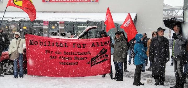 Demonstrierende im Schneegestöber, rote Fahnen, Transparent: «Mobilität für Alle. Für ein Sozialtkcket, das diesen Namen verdient!».