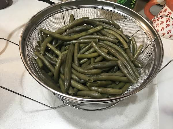 Metal Strainer Bowl Filled With Cooked Green Beans.