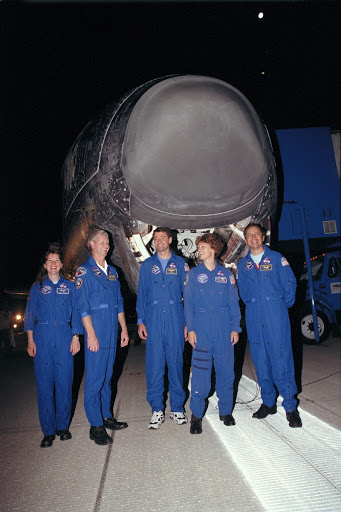 Members pose in front of the Space Shuttle Columbia following the night landing on runway 33 at Kennedy Space Center's Shuttle Landing Facility.