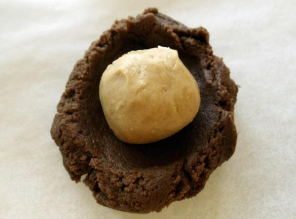 FORM COOKIES: Scoop 1 tablespoon of the dough. Make an indentation in the center...