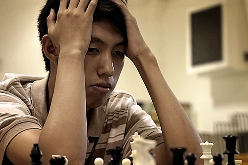 Andy Ko contemplating his next move. Regional Chess Tournament, Orange Walk Town.