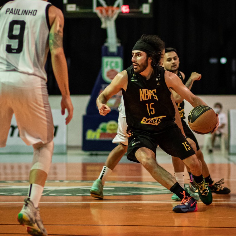 A basketball player dribbling the ball  Description automatically generated with medium confidence