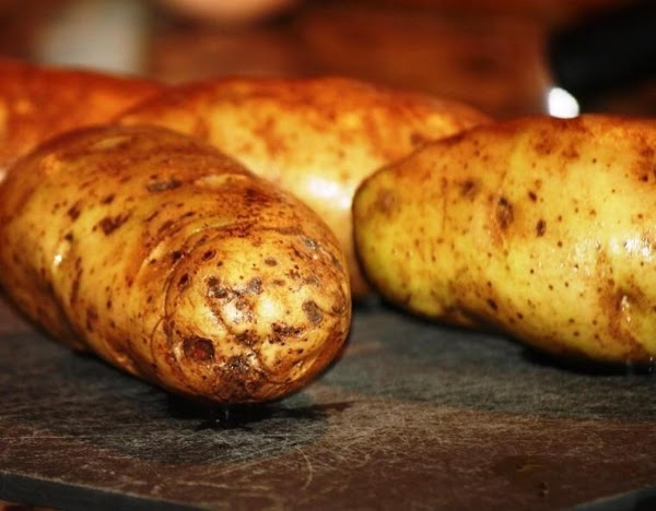 Wash and scrub potatoes, pat dry. Rub potatoes with butter and place in baking...