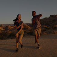 Two people running outside in a canyon
