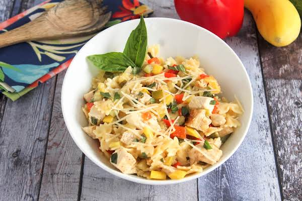 A Bowl Of Chicken And Pasta With Summer Vegetables.