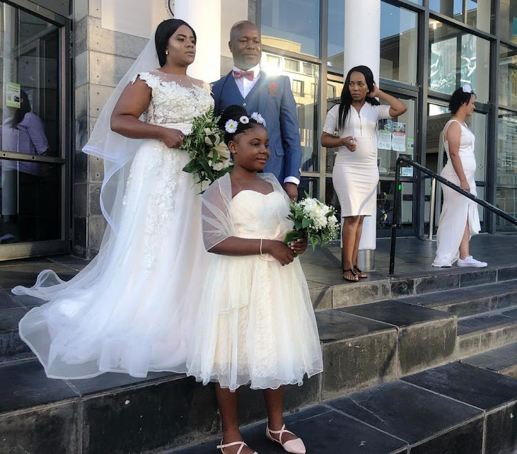 Sandra Mushovhani and Eucriff Ramachuphu, with their nine-year-old daughter Unarine, at the Nelson Mandela Gateway, at the V&A Waterfront in Cape Town, before setting sail for their Robben Island wedding on February 14 2019.