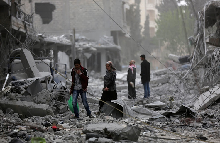 People walk through debris in a town in war-shattered Syria. REUTERS/Khalil Ashawi