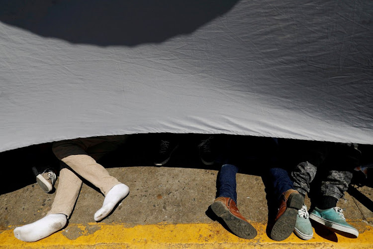 Central American migrants protect themselves from the sun as they wait on the bridge that connects Mexico and Guatemala.
